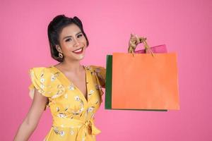 vacker asiatisk kvinna med färgade shoppingpåsar
