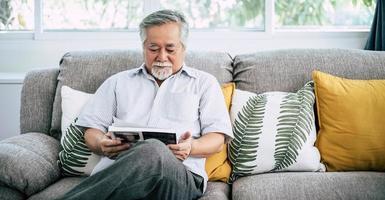 gammal man läser i vardagsrummet foto