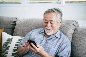 äldre man använder smartphone foto
