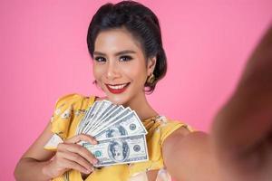glad moderiktig kvinna som håller pengar