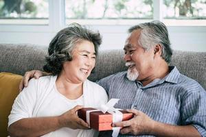 äldre par med överraskning presentask i vardagsrummet foto