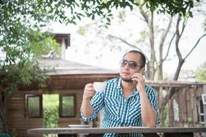 ung affärsman som använder smartphonen medan han arbetar i hemträdgården foto