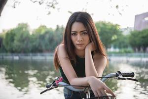 vacker ung kvinna som cyklar i grön park