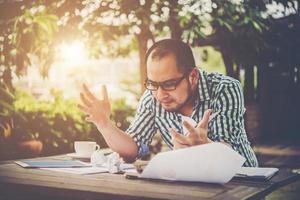 stressad affärsman med papper och diagram som sitter vid bordet hemma