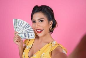 glad moderiktig kvinna som håller pengar för shopping