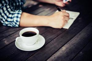 närbild av affärsmannen som använder smartphonen medan han arbetar på kaféet foto