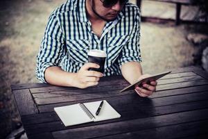 ung man som använder den digitala minnestavlan medan han dricker kaffesammanträde hemma i trädgården foto
