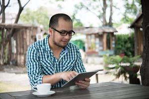 affärsman arbetar på minnestavlan medan du sitter hemma vid träbord foto