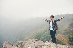 vandrare med ryggsäck som står på toppen av ett berg med upphöjda händer