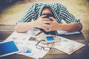 trött arbetande man som sover på arbetsplatsen full av arbete