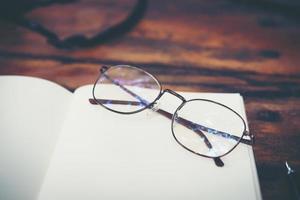 arbetsyta skrivbord med glasögon och anteckningsbok med kopia utrymme bakgrund foto