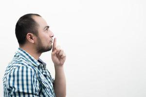 ung man gör tystnad gest isolerad på vit bakgrund.