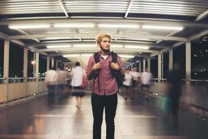 stilig skäggig man med ryggsäck som står på gatan som reser på natten