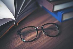 glas på träbord med boken