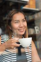 asiatisk kvinna som kopplar av med kaffe på kaféet