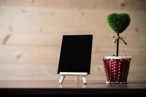 tom svart tavla, hjärtaträd på träbakgrund, med kopieringsutrymme foto