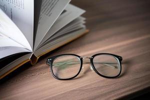 hög med bok och glasögon på träbordet foto