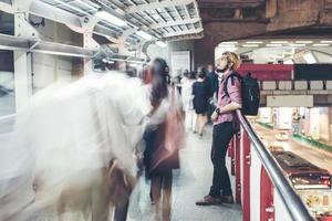 hipster skäggig man står i tågstationen med människor rörelse bakgrund