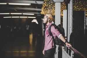 stilig skäggig man med ryggsäck som står på gatan när han reser på natten