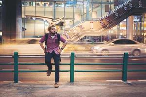hipster skäggig man sitter på räcke med bil rörelse bakgrund