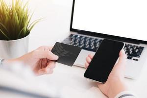 kvinnas hand som håller en smartphone och kreditkort för online-shopping foto