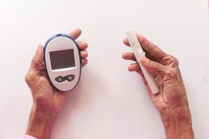 äldre kvinnor diabetiker mäter en glukosnivå hemma foto