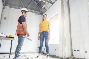 två personer som arbetar med husbyggande