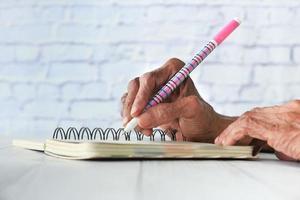 närbild av äldre kvinnor som skriver i ett anteckningsblock