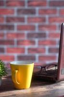 gul mugg på ett skrivbord foto