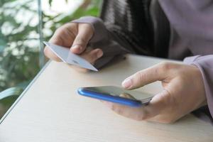kvinna som håller ett kreditkort och använder smart telefon för att handla online foto