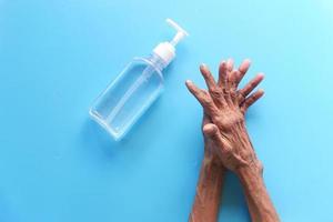 person som använder handdesinfektionsmedel på en blå bakgrund foto