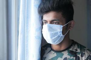 en ung man med skyddande mask som tittar genom fönstret