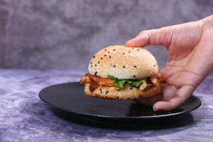hand som håller en nötköttburger på ett bord på nära håll