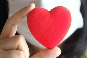 kvinnor som håller rött hjärta med kopieringsutrymme foto