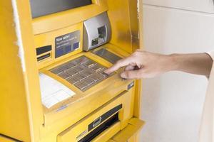 närbild av en hand som trycker på knappar på en bankomat