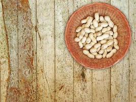 jordnötter i rotting korg på trä bakgrund foto