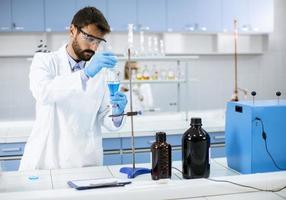 forskare som arbetar med blå vätska vid laboratorieglas