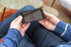 närbild av en man som håller en mobil smartphone foto