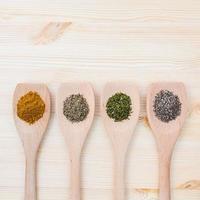 torkade kryddor i träskedar på en träbakgrund foto