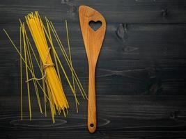 spagettinudlar och ett träredskap foto