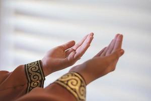 händerna på en muslimsk eller islamisk kvinna som gör en gest medan hon ber hemma