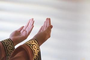 händerna på en muslimsk eller islamisk kvinna som gör en gest medan hon ber hemma foto