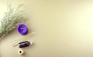 lavendel doftolja i en flaska med lila ljus, träpinnar och torra blommor platt låg på ett bord foto