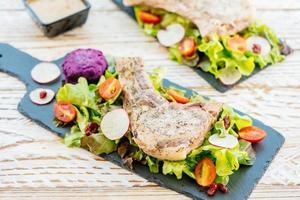 grillad bbq fläskkotlett biff på svart tallrik med grönsaker foto