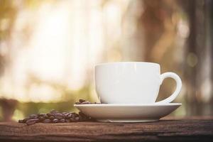kaffekopp och kaffebönor på träbord