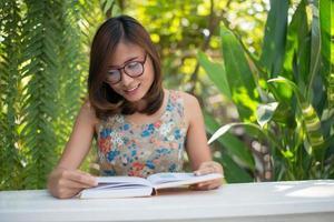 ung hipster kvinna läser böcker i hem trädgård med naturen
