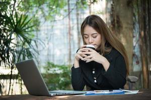 affärskvinna som pratar i telefon och använder sitt bärbara datorsammanträde på ett bord hemma