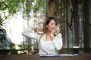 ung affärskvinna som sträcker sig och gäspar på arbetsplatsen foto