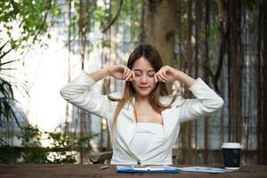 affärskvinna som sträcker sig och gäspar på arbetsplatsen foto