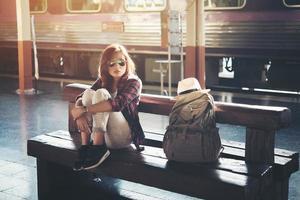 hipster kvinna backpacking sitter på tågstationen foto